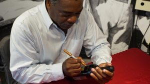 """'Eddie signs a limited edition bottle of """"The Roundtripper.""""' from the web at 'http://baberuthmuseum.org/wp-content/uploads/2015/09/DSC00642-300x169.jpg'"""